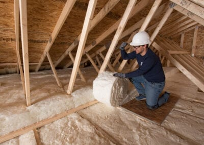 Austin Company | installing white fiberglass insulation in attic of residential home