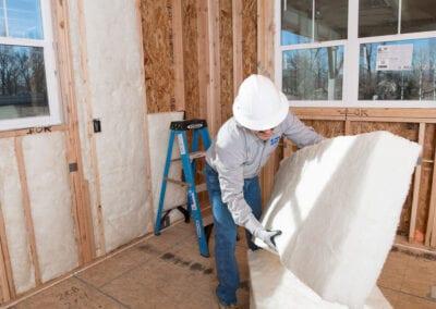 Austin Company   installing white fiberglass insulation in home